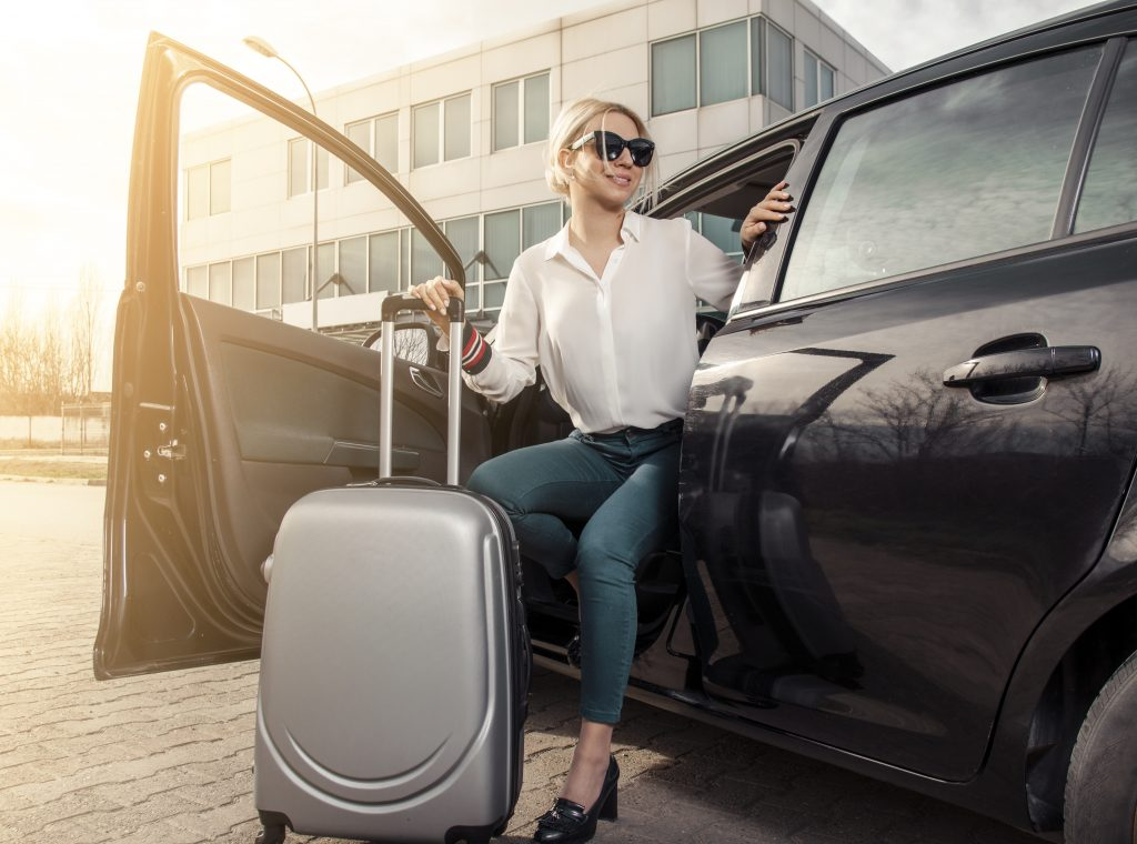 Attractive young businesswoman with luggage getting out of the car